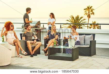 Beautiful group of people socialising on a rooftop with some alcoholic beverages and barbecue grill going, while soaking is some summer sun outdoors.