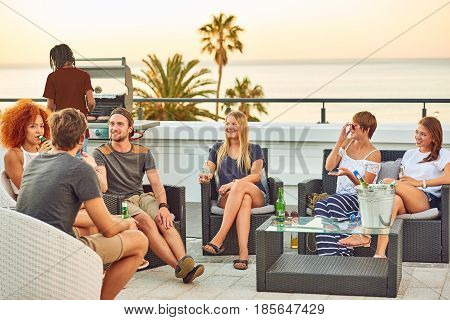 Attractive group of young people socialising on a rooftop with a view of the ocean while enjoying some alcoholic beverages and a gas barbecue on a warm summer sunset. poster