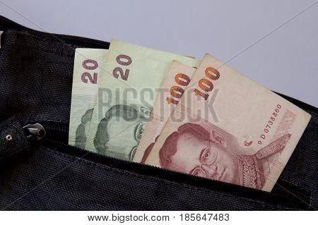 Thai baht notes in a black bag.