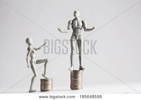 Income Inequality Concept Shown With Realistic Male And Female Figurines And Piles Of Coins.