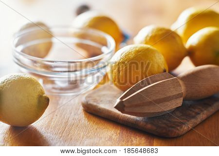lemons with wooden reamer ready to be juiced