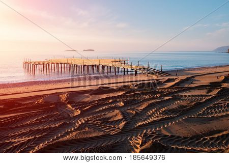 Installation of summer terrace on beach. Breathtaking view on mediterranean sea. Imported sand on a stony beach. Track of wheels