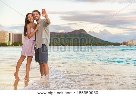 Couple walking on beach at sunset taking selfie picture on mobile phone relaxing together on Waikiki beach, Honolulu, Hawaii travel vacation. Romantic holiday destination for honeymoon.