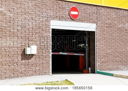 Departure from the underground parking. Gate for exit. The barrier is closed. The sign of entry is prohibited. Gates are automatic. Shopping center.