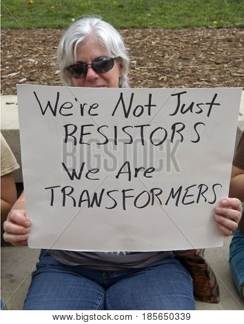 Asheville, North Carolina, USA - April 22, 2017: Woman holds a sign saying