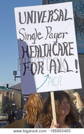 Asheville, North Carolina, USA - February 25, 2017: Woman holds a sign saying