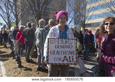 "Asheville North Carolina USA - February 25 2017: Woman amid a crowd of protesters wearing a Pussyhat and lab coat holds a colorful sign saying ""Doctors Demand Healthcare For ALL"" at an Obamacare (Affordable Care Act) rally on February 25 2017 in downtown"