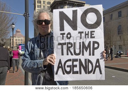 Asheville North Carolina USA - February 25 2017: Male political demonstrator at an Affordable Care Act rally holds a sign saying