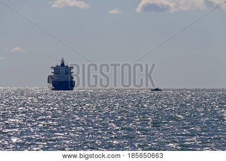 A large ship being intercepted by a small tug boat on the open waters of the Chesapeake Bay on a sunny day