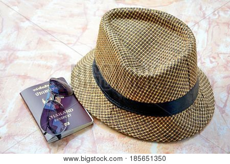 Prepare a passport visor hat for travel on stone table.