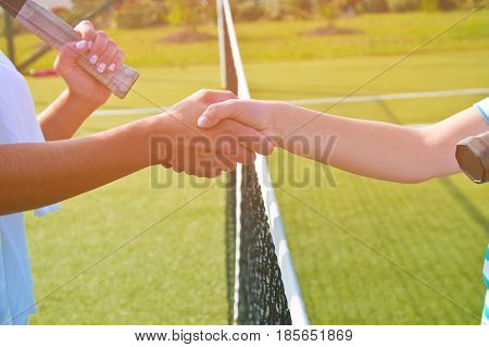 Tennis players shake hands before and after the tennis match.