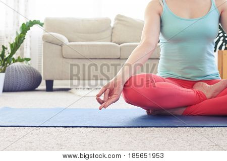 Cropped shot of slim girl meditating in lotus pose on yoga mat in living room with copy space