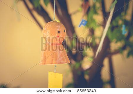 Orange chasing rain Japanese doll hanging on branches tree. (Autumn filter effect)