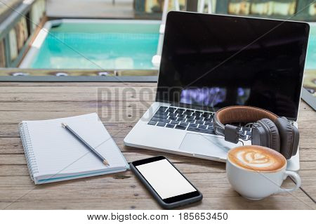 Laptop Coffee Cup Notepad Smartphone And Headphone At Poolside