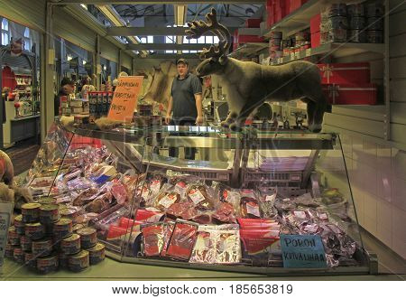 Oulu, Finland - April 11, 2017: man is selling meat and sausages at the market in Oulu, Finland