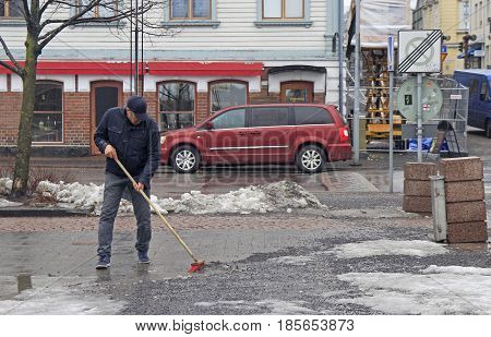 Oulu, Finland - April 11, 2017: man is cleaning up the market square in Oulu, Finland
