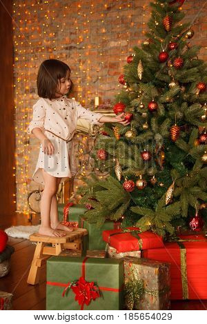 Little girl is decorating christmas tree with the presents underneath it