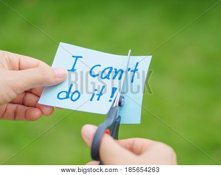 Women using scissors to remove the word can't to read I can do it concept for self belief positive attitude and motivation