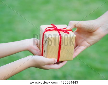 holidays present christmas childhood and happiness concept - close up of child and mother hands with gift box over green background