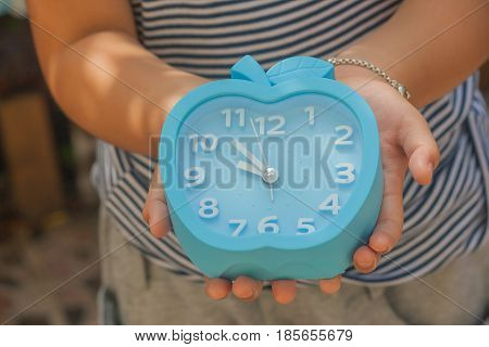 Time Management Concept : Cute little girl's hand holding alarm clock. (Autumn filter effect)