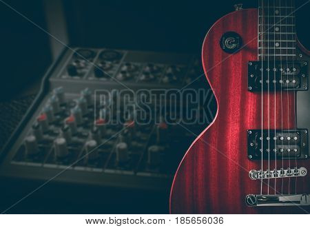 Red electric guitar and classic amplifier on a dark background.