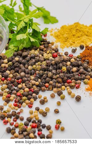 Fragrant black pepper on a white background, this is a common spice with useful properties obtained from seeds of plants of the genus Pepper
