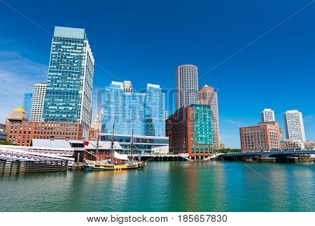Boston - June 2016, MA, USA: Boston skyline, old historic ship in Tea Party museum and modern buildings in downtown reflected in the water of Boston harbor