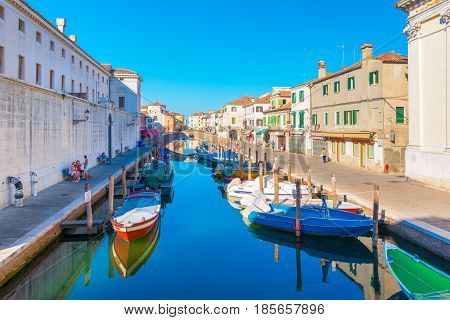 Chioggia - September 2016, Veneto, Italy: Canal with boats on water in Chioggia historic center. People are walking, sitting on benches near the old buildings and houses in Venetian style