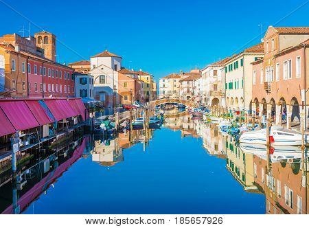Chioggia - September 2016, Veneto, Italy: Cityscape of Chioggia historic city center. Canal Vena with boats lying on water and colored houses in traditional architectural style