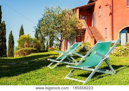 Chaise Lounges On The Green Meadow Of A Country House