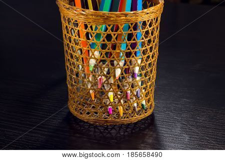 Sharp tips of colored pencils sharpen from sections of a wicker tube, on a dark wooden background