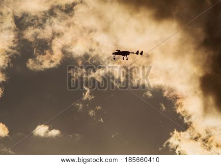 Unmanned aerial vehicle (UAV) in the sky in sunset.