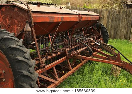 Old Grunge Seeding Machines Standing On The Grass After The End Of Sowing. Old Equipment. Decline In