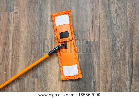 Modern mop on wooden laminated floor at home. Cleaning concept