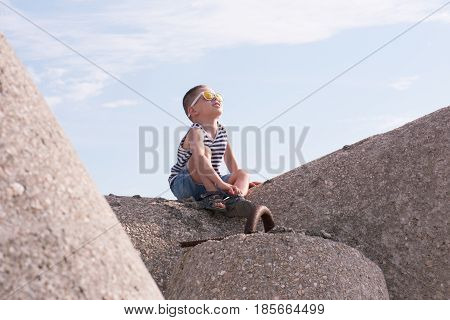 cute smiling little boy in sunglasses sailor stripes vest and shorts sitting on a breakwater and enjoying the sun looking up