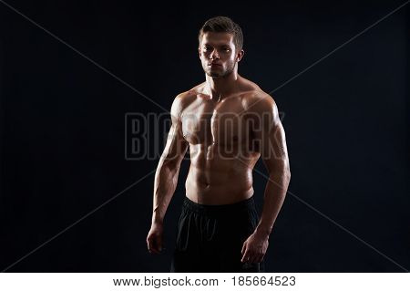 Handsome strong athletic young man fitness model showing off his abs six-pack posing shirtless on black background copyspace athletics body torso masculinity sexy sportsman sport fitness bodybuilder.