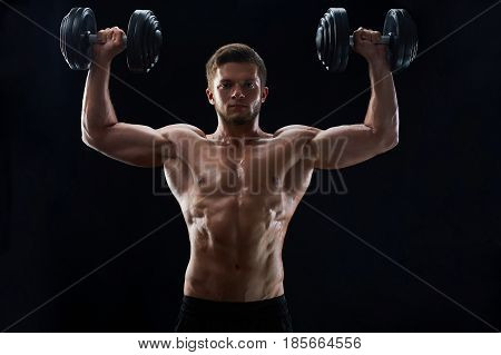 Horizontal shot of a sporty young shirtless man exercising with heavy dumbbells on black background fitness gym confidence masculinity lifestyle bodybuilding shaping toning ripped abs abdominal torso.