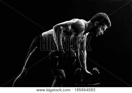 Monochrome low key lighting shot of a strong fit and toned young man exercising with dumbbells doing triceps workout gym motivation masculinity active athletics physique confidence focusing.