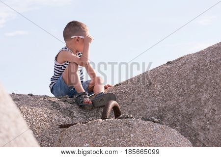 healthy little boy in sunglasses sailor stripes vest and shorts sitting on a breakwater looking aside in summer