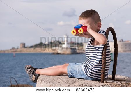 smiling little boy in a vest and shorts looking into the distance through binoculars sitting on a concrete breakwater against the background of the sea and the shore with lighthouse