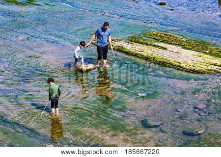 KEELUNG TAIWAN - APRIL 04: Taiwanese family fishing in clean shallow water in the seaside area of Keelung on April 04 2017 in Keelung