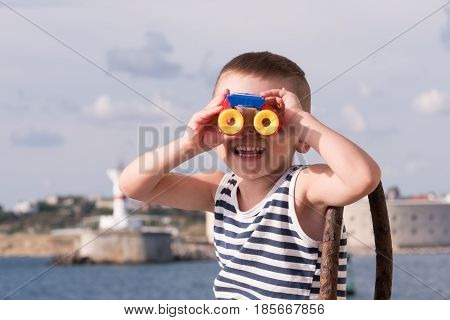 cheerful little boy in a vest looking into the distance through binoculars sitting against the background of the ocean and shore