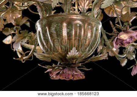 Chandelier close-up classic bronze with curly lampshades flowers and gold leaves. on black background isolated