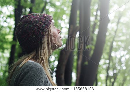 horizontal side view portrait of Caucasian young woman with long blonde hair and colorful wool hat standing in a green forest and looking up