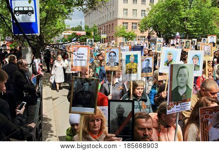 KURSK RUSSIA - May 92017: People in the crowd participating in Immortal Regiment procession in Victory Day. Thousands of people marching toward the Red Square with flags and portraits.
