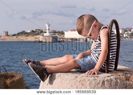 cute little boy in sunglasses and a vest sitting on concrete breakwater with sea and shore with lighthouse background
