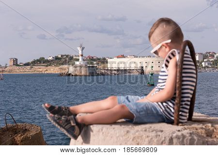 one little boy in sunglasses and a vest sitting on concrete breakwater with sea and shore with lighthouse background with focus on background