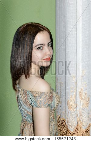 photography with scene of the young beautiful girl costing near white blinds