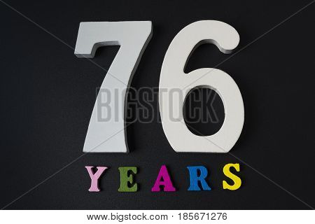 Letters And Numbers Seventy-six Years On A Black Background.