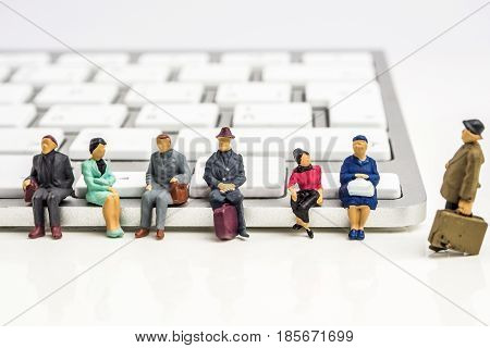 closeup of miniature figurine of people sitting on white keyboard on white background